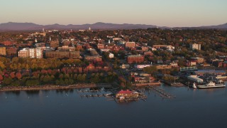 DX0002_225_013 - 5.7K stock footage aerial video orbit buildings and park in downtown behind marinas at sunset, Burlington, Vermont
