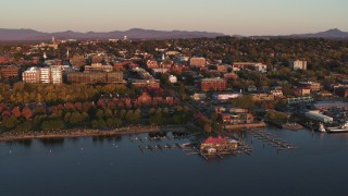 DX0002_225_014 - 5.7K stock footage aerial video of buildings and park in downtown behind a marina at sunset, Burlington, Vermont