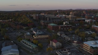 DX0002_225_024 - 5.7K stock footage aerial video descend while focused on downtown office buildings at sunset, Burlington, Vermont