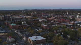 DX0002_225_025 - 5.7K stock footage aerial video reverse view of downtown office buildings at twilight, Burlington, Vermont