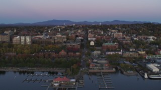 DX0002_225_030 - 5.7K stock footage aerial video approach and flyby downtown buildings and a marina at twilight, Burlington, Vermont