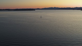 DX0002_225_033 - 5.7K stock footage aerial video approach sailboat on Lake Champlain at twilight, Burlington, Vermont