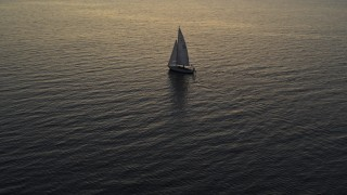DX0002_225_034 - 5.7K stock footage aerial video approach and orbit sailboat on Lake Champlain at twilight, Burlington, Vermont