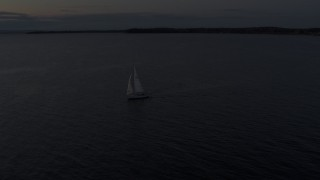 DX0002_225_035 - 5.7K stock footage aerial video of a sailboat on Lake Champlain at twilight, Burlington, Vermont