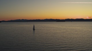 DX0002_225_036 - 5.7K stock footage aerial video of flying away from a sailboat on Lake Champlain at twilight, Burlington, Vermont