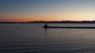 DX0002_226_002 - 5.7K stock footage aerial video of flying low to approach and fly over lighthouse on Lake Champlain at twilight, Burlington, Vermont