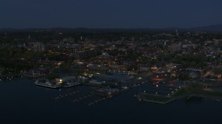 DX0002_226_019 - 5.7K stock footage aerial video a stationary view of city's downtown area and a marina at night, Burlington, Vermont