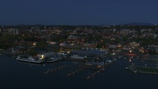 DX0002_226_020 - 5.7K stock footage aerial video descend past the city's downtown area and a marina at night, Burlington, Vermont