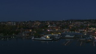 DX0002_226_021 - 5.7K stock footage aerial video fly away from the city's downtown area and a marina at night, Burlington, Vermont