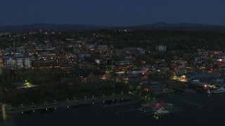 DX0002_226_025 - 5.7K stock footage aerial video focus on the city's downtown area lit up for the night while flying away, Burlington, Vermont