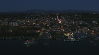DX0002_226_027 - 5.7K stock footage aerial video focus on the city's downtown area lit up for the night while approaching, Burlington, Vermont
