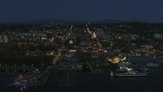 DX0002_226_028 - 5.7K stock footage aerial video focus on the city's downtown area lit up for the night, fly away from marinas, Burlington, Vermont