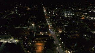 DX0002_226_038 - 5.7K stock footage aerial video circling and flying away from office buildings on Battery Street lit up for nighttime, Burlington, Vermont