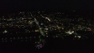 DX0002_226_042 - 5.7K stock footage aerial video of flying away from and orbiting office buildings and streets in downtown lit up for nighttime, Burlington, Vermont