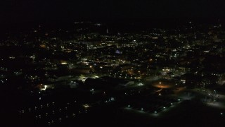 DX0002_226_044 - 5.7K stock footage aerial video of circling around city buildings in downtown lit up for nighttime, Burlington, Vermont