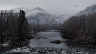 DX0002_227_001 - 5.7K stock footage aerial video of flying low over the river toward snowy mountains in Leavenworth, Washington