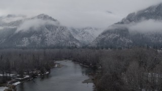 DX0002_227_002 - 5.7K stock footage aerial video of ascending away from the river and snowy mountains in Leavenworth, Washington