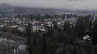DX0002_227_011 - 5.7K stock footage aerial video ascend from trees for view of the town, Leavenworth, Washington