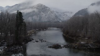 DX0002_227_013 - 5.7K stock footage aerial video of following the river toward snowy mountains in Leavenworth, Washington
