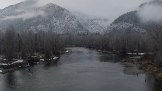 DX0002_227_014 - 5.7K stock footage aerial video of following the river to approach snowy mountains in Leavenworth, Washington