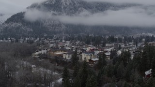 DX0002_227_021 - 5.7K stock footage aerial video focus on Leavenworth by snowy mountains, Washington during descent
