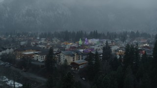 DX0002_227_033 - 5.7K stock footage aerial video fly over trees to reveal town with tall Christmas trees, Leavenworth, Washington