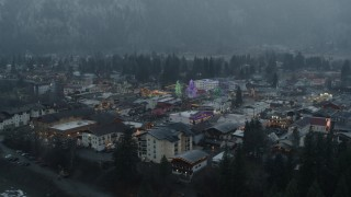 DX0002_227_035 - 5.7K stock footage aerial video of flying away from tall Christmas trees at the center of town, Leavenworth, Washington