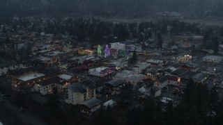 DX0002_227_048 - 5.7K stock footage aerial video approaching a small town decorated with Christmas trees and lights, Leavenworth, Washington
