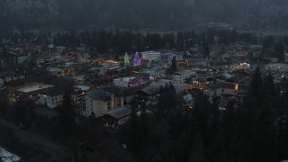 DX0002_227_049 - 5.7K stock footage aerial video fly away from a small town decorated with Christmas trees and lights, Leavenworth, Washington