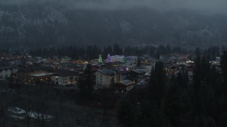 DX0002_227_050 - 5.7K stock footage aerial video ascend from trees to reveal a small town decorated with Christmas trees and lights, Leavenworth, Washington