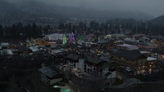 DX0002_227_052 - 5.7K stock footage aerial video circling a small town decorated with Christmas trees and lights, Leavenworth, Washington
