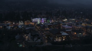 DX0002_228_002 - 5.7K stock footage aerial video of circling a small town with Christmas trees and lights at twilight, Leavenworth, Washington