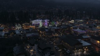 DX0002_228_003 - 5.7K stock footage aerial video of an orbit of a small town with Christmas trees and lights at twilight, Leavenworth, Washington