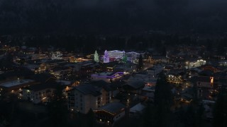DX0002_228_006 - 5.7K stock footage aerial video ascend from trees to reveal Christmas trees and lights at night in Leavenworth, Washington