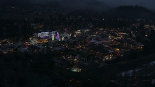 DX0002_228_009 - 5.7K stock footage aerial video of an orbit of Christmas trees and lights at night in Leavenworth, Washington