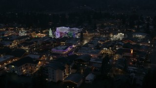 DX0002_228_013 - 5.7K stock footage aerial video descend and slowly fly away from Christmas trees and lights at night in Leavenworth, Washington