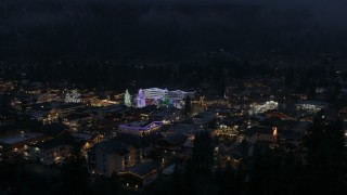 DX0002_228_014 - 5.7K stock footage aerial video ascend to reveal town with Christmas trees and lights at night in Leavenworth, Washington