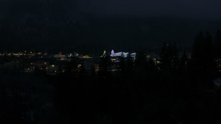 DX0002_228_019 - 5.7K stock footage aerial video ascend to reveal and approach Christmas trees and lights at night in Leavenworth, Washington