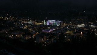 DX0002_228_020 - 5.7K stock footage aerial video reverse view of Christmas trees and lights at night, descend behind trees, Leavenworth, Washington