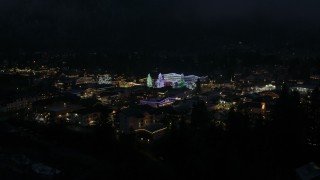 DX0002_228_021 - 5.7K stock footage aerial video ascend from trees to reveal Christmas trees and lights at night, Leavenworth, Washington