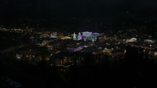 DX0002_228_027 - 5.7K stock footage aerial video of trees and buildings with Christmas lights at night, Leavenworth, Washington