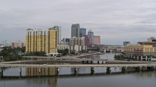 DX0003_229_038 - 5.7K stock footage aerial video fly over a bridge and ascend toward the city skyline behind a condo complex, Downtown Tampa, Florida