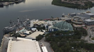 DX0003_230_031 - 5.7K stock footage aerial video fly away from and orbit a warship museum and aquarium in Tampa, Florida
