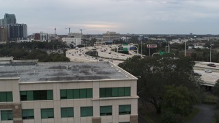 DX0003_231_001 - 5.7K stock footage aerial video ascend near office building to reveal freeway traffic in Tampa, Florida