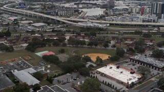 DX0003_231_014 - 5.7K stock footage aerial video orbit and fly away from apartment buildings by elementary school, Tampa, Florida