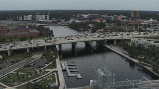 DX0003_231_029 - 5.7K stock footage aerial video orbit and approach traffic on a bridge spanning the river in Tampa, Florida