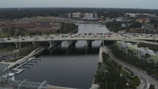 DX0003_231_030 - 5.7K stock footage aerial video fly away from traffic on a bridge spanning the river in Tampa, Florida