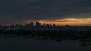 DX0003_231_054 - 5.7K stock footage aerial video ascending toward Downtown Tampa skyline from the bay at sunset, Florida