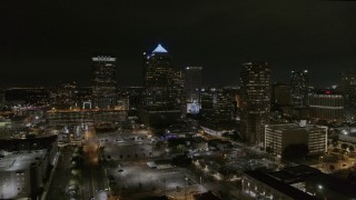 DX0003_232_027 - 5.7K stock footage aerial video orbit and fly away from skyscrapers at night in Downtown Tampa, Florida