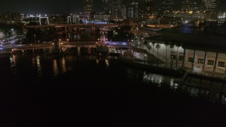 DX0003_232_055 - 5.7K stock footage aerial video fly away from police cars on a bridge by convention center at night in Downtown Tampa, Florida